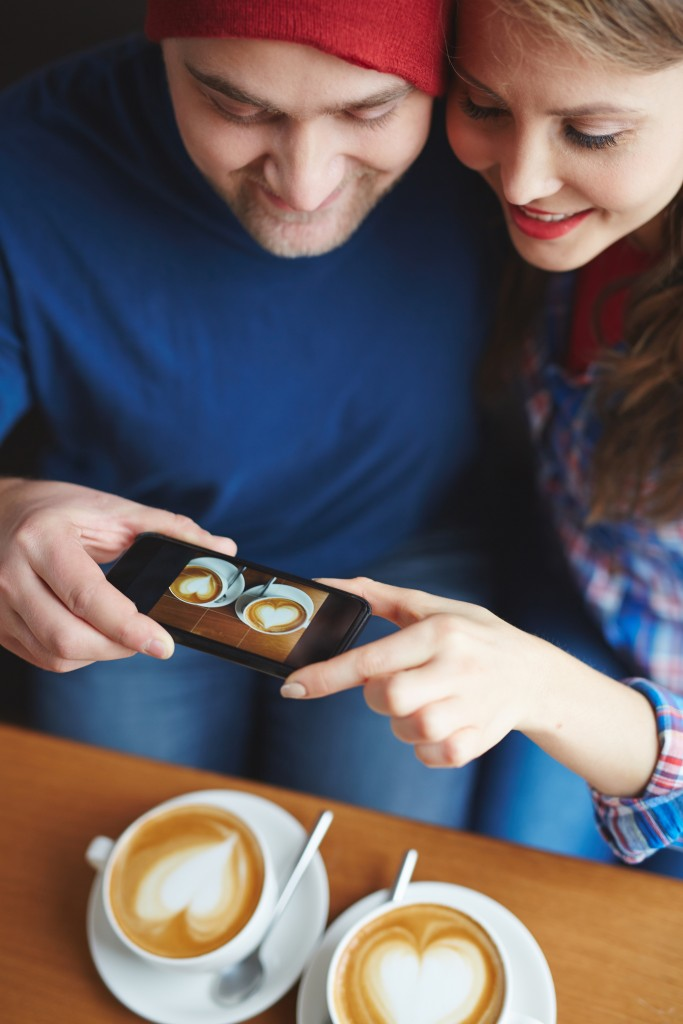 Amorous dates making photo of their coffee in cafe