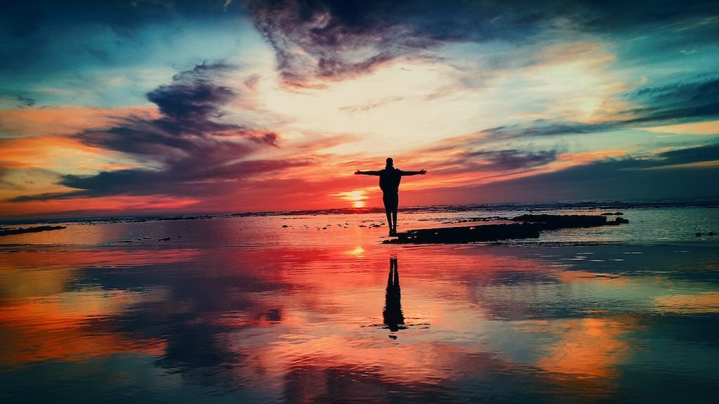 Person standing by the ocean at sunset, with arms outstretched